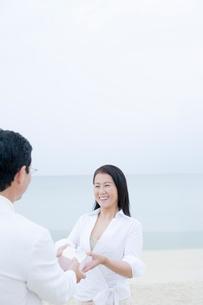 海辺でプレゼントの受け渡しをする夫婦の写真素材 [FYI02948161]