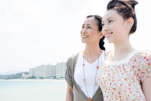 海辺に立つ笑顔の母と娘の写真素材 [FYI02948163]