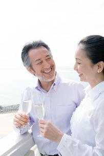 ベランダでワイングラスを手に微笑む夫婦の写真素材 [FYI02948237]