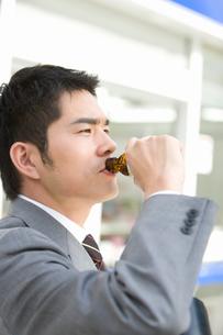 コンビニの前で栄養ドリンクを飲む男性の写真素材 [FYI02948614]
