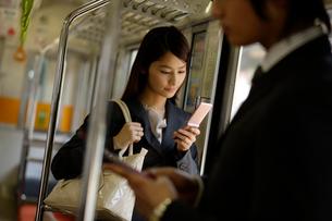 電車内で携帯電話を見ているOLの写真素材 [FYI02948763]