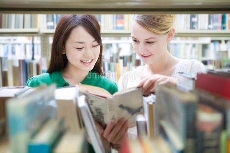 図書室で本を見るふたりの女子学生の写真素材 [FYI02948950]