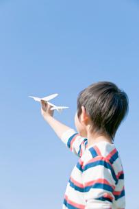 紙飛行機を飛ばそうとする男の子の写真素材 [FYI02949076]