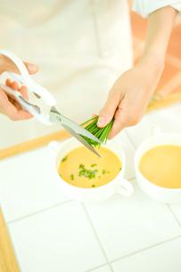 スープの浮き身にチャイブを刻む女性の手の写真素材 [FYI02949099]