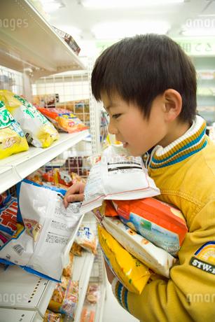 コンビニでお菓子を抱える男の子の写真素材 [FYI02949182]