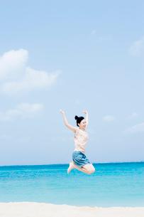 海辺でジャンプをする女性の写真素材 [FYI02949638]