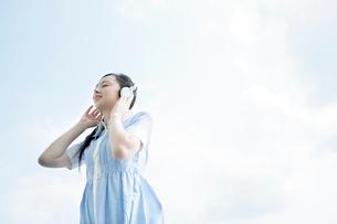 青空の下で音楽を聞く女性の写真素材 [FYI02949750]