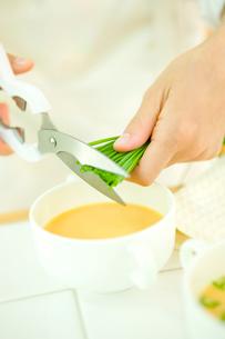 スープの浮き身にチャイブを刻む女性の手の写真素材 [FYI02949975]