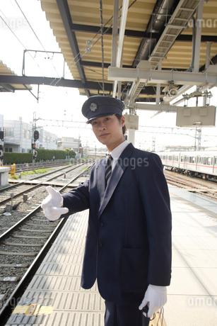 駅のホームで合図をする駅員の写真素材 [FYI02950023]