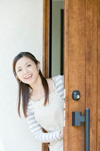 玄関から顔を出す笑顔の女性の写真素材 [FYI02950251]