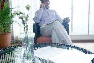 読書をしながら携帯電話で会話する男性の写真素材 [FYI02950267]