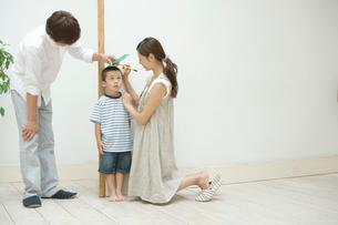 息子の身長を測る両親の写真素材 [FYI02950461]