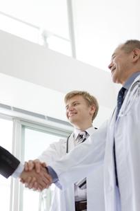 握手をする医師とビジネスマンの手元の写真素材 [FYI02951439]