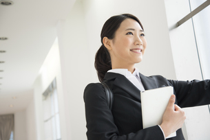 スケジュール帳を持っているスーツ姿の女性の写真素材 [FYI02951659]