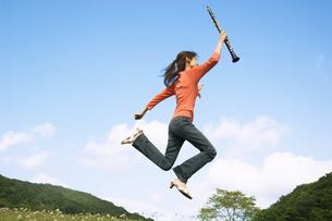 クラリネットを持ってジャンプする女性の写真素材 [FYI02951897]