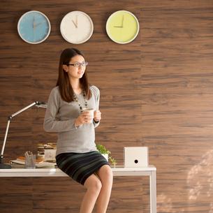 コーヒーカップを持ち机に寄りかかるビジネスウーマンの写真素材 [FYI02951968]