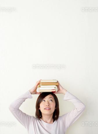 本を頭に載せた女性の写真素材 [FYI02952461]