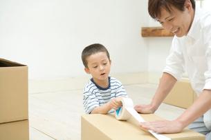 ダンボール箱にガムテープを貼る父と息子の写真素材 [FYI02953015]