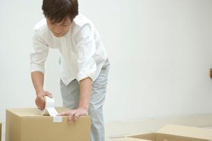 ダンボール箱にガムテープを貼る男性の写真素材 [FYI02953499]