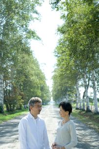 一本道に佇むシニア夫婦の写真素材 [FYI02953509]
