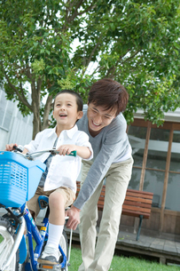 父親と自転車に乗る練習をする男の子の写真素材 [FYI02953601]
