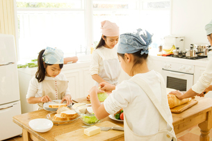 キッチンで料理を作る日本人の娘4人の写真素材 [FYI02953667]