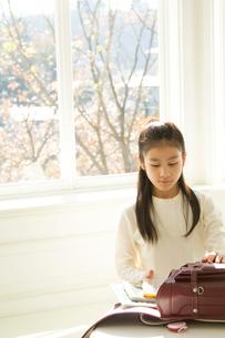 窓際でランドセルを開ける日本人の娘の写真素材 [FYI02953678]