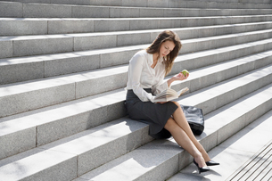 Young woman reading and eating on stepsの写真素材 [FYI02953682]