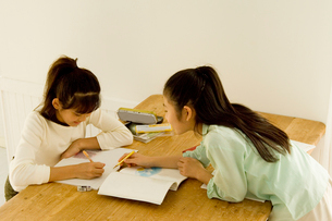 室内のテーブルで宿題をする日本人の娘2人の写真素材 [FYI02953736]