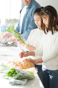 キッチンで料理中の日本人の父親と娘2人の写真素材 [FYI02953802]