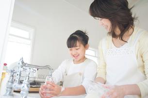 キッチンで洗い物をする日本人の母親と娘の写真素材 [FYI02953811]