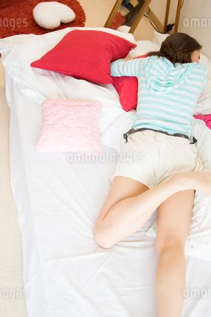 布団に横になる20代日本人女性の写真素材 [FYI02953848]