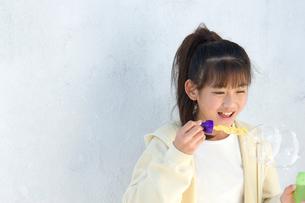 壁際でシャボン玉をする日本人の女の子の写真素材 [FYI02953901]