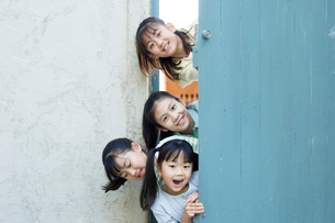 扉から顔を出す日本人の女の子たちの写真素材 [FYI02953946]
