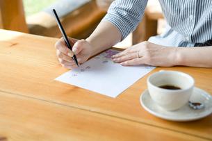 手紙を書くシニア女性の手元の写真素材 [FYI02954029]