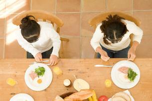 キッチンで朝食を取る日本人の娘2人の写真素材 [FYI02954050]