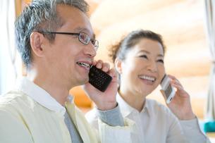 携帯電話で話すシニア夫婦の写真素材 [FYI02954353]