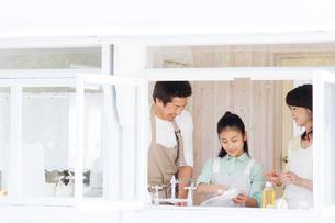 キッチンで洗い物をする日本人の夫婦と娘の写真素材 [FYI02954545]