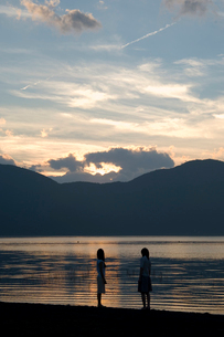 夕暮れの湖畔に立つ2人の20代日本人女性の写真素材 [FYI02954831]