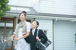 母親と腕を組んで歩く女の子の写真素材 [FYI02954871]
