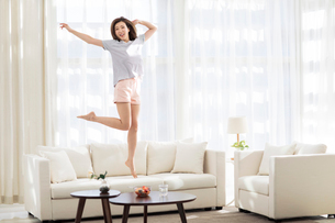 Cheerful young Chinese woman jumping on sofaの写真素材 [FYI02955256]