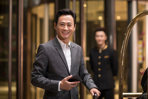 Cheerful Chinese businessman holding a smart phoneの写真素材 [FYI02955269]