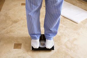 Mature man on bathroom scaleの写真素材 [FYI02956056]