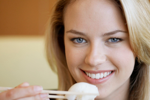 Young woman eating with chopsticksの写真素材 [FYI02956233]