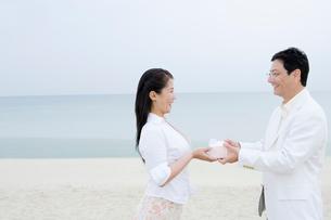 海辺でプレゼントの受け渡しをする夫婦の写真素材 [FYI02956290]