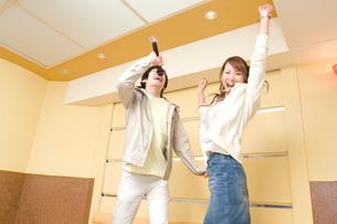 カラオケで歌うカップルの写真素材 [FYI02956544]
