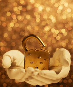 Golden Padlock on Hand Sculptureの写真素材 [FYI02956707]