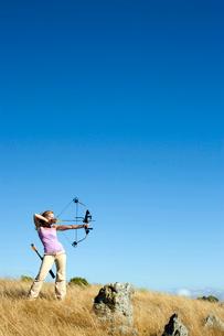 Young woman arrow shooting in fieldの写真素材 [FYI02956724]