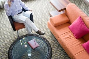 読書をしながら携帯電話で会話する男性の写真素材 [FYI02956950]