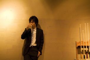 壁にもたれてお酒を飲むビジネスマンの写真素材 [FYI02957534]